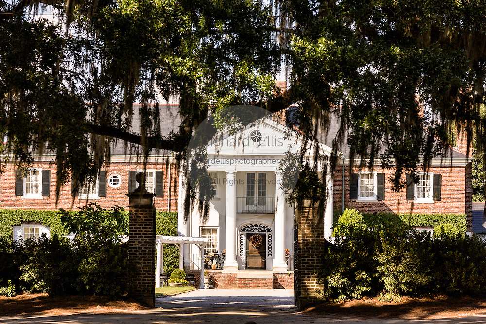 The Colonial Revival plantation house surrounded by live oak trees draped with spanish moss at Boone Hall Plantation in Mt Pleasant, South Carolina.