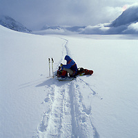USA, Alaska, Denali National Park, (MR) Rudiger Stuiss rests on sled along Kahiltna Glacier while climbing Mt. McKinley