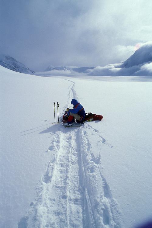 USA, Alaska, Denali National Park, (MR) Rudiger Stuiss rests on sled along Kahiltna Glacier while climbing Mt. McKinley