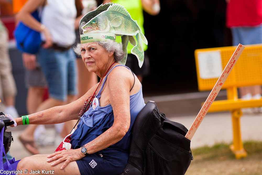"01 SEPTEMBER 2011 - ST. PAUL, MN:  A woman wearing fish hat from Gander Mountain, a Minnesota based sporting goods chain, rides through the fair grounds at the Minnesota State Fair. The Minnesota State Fair is one of the largest state fairs in the United States. It's called ""the Great Minnesota Get Together"" and includes numerous agricultural exhibits, a vast midway with rides and games, horse shows and rodeos. Nearly two million people a year visit the fair, which is located in St. Paul.   PHOTO BY JACK KURTZ"