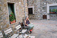 ACCIAROLI, ITALY - 14 SEPTEMBER 2018: An elderly woman sits in front of her house in Acciaroli, a small fishing village in the municipality of Pollica, Italy, on September 14th 2018.<br /> <br /> To understand how people can live longer throughout the world, researchers at University of California, San Diego School of Medicine have teamed up with colleagues at University of Rome La Sapienza to study a group of 300 citizens, all over 100 years old, living in Acciaroli (Pollica), a remote Italian village nestled between the ocean and mountains in Cilento, southern Italy.<br /> <br /> About 1-in-60 of the area's inhabitants are older than 90, according to the researchers. Such a concentration rivals that of other so-called blue zones, like Sardinia and Okinawa, which have unusually large percentages of very old people. In the 2010 census, about 1-in-163 Americans were 90 or older.