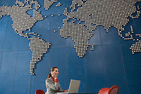 Business woman using mobile phone and laptop in office with world map on wall