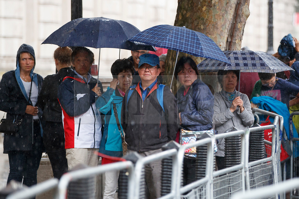 © Licensed to London News Pictures. 27/06/2017. London, UK. A group of tourists take shelter from the rain on Whitehall in London on Tuesday, 27 June 2017. Photo credit: Tolga Akmen/LNP