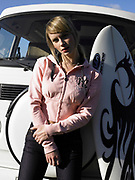 Young woman leaning against front of a van with surfboard next to her.