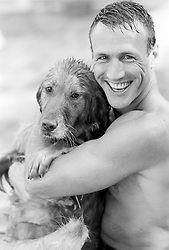 Shirtless man smiling holding his wet dog
