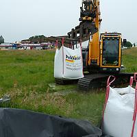 DALFSEN - Zandzakken<br /> Foto: Loonwerker Pekkeriet plaatst vanmiddag dertig 'bigbags' met zand om de kermis te beschermen tegen het plotselingen hoogwater in de Vecht.<br /> FFU PRESS AGENCY COPYRIGHT SANDER UIJLENBROEK