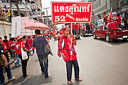 "Mar. 27, 2010 - BANGKOK, THAILAND:  A Red Shirt stands in the middle of a Bangkok street as other Red Shirts march past him Saturday, March 27. More than 80,000 members of the United Front of Democracy Against Dictatorship (UDD), also known as the ""Red Shirts"" and their supporters marched through central Bangkok March 27 during a series of protests against and demand the resignation of current Thai Prime Minister Abhisit Vejjajiva and his government. The protest is a continuation of protests the Red Shirts have been holding across Thailand. They support former Prime Minister Thaksin Shinawatra, who was deposed in a coup in 2006 and went into exile rather than go to prison after being convicted on corruption charges. Thaksin is still enormously popular in rural Thailand.    PHOTO BY JACK KURTZ"