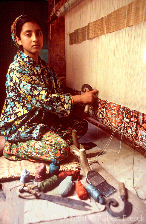 INDIA, CRAFTS a young girl weaving a traditional carpet  on a loom in her village home in Srinagar,  Kashmir