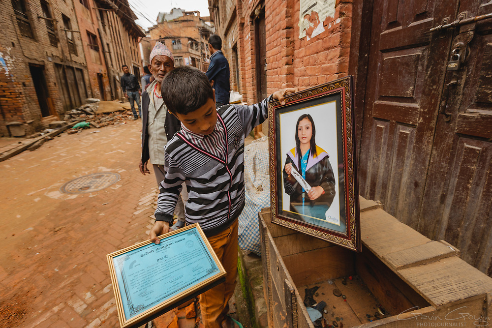 A boy salvaging belongings from a family home that was destroyed during the 2015 Nepal earthquake.