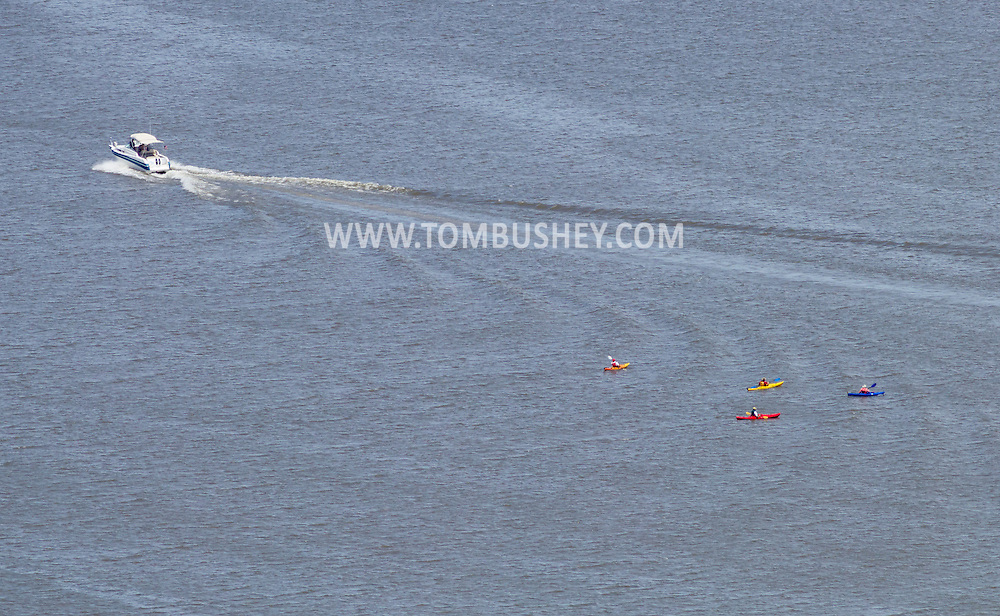 Cornwall-on-Hudson, New York - A motor boat moves north after passing four kayaks on the Hudson River in a view from the scenic overlook on Storm King Highway on June 20, 2014. ©Tom Bushey / The Image Works