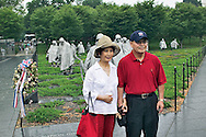 Asian visitors posing for pictures in front of the Vietnam Veterans Memorial, Washington, D.C.