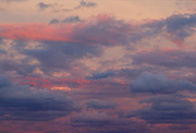 An evening sky is filled with clouds of pink and blue hues.