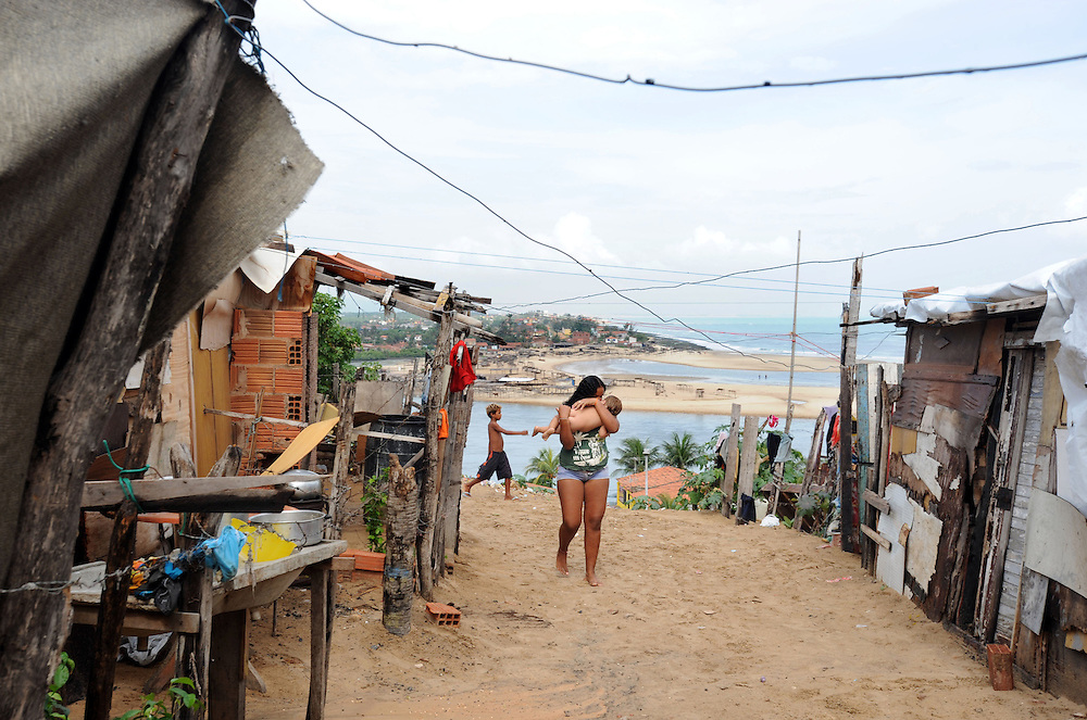 A woman and her baby who live in a favela which is built on sand dunes and is at risk of sliding into the sea due to frequent flooding in Fortaleza, Ceasa province, Brazil.