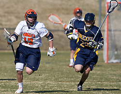 Virginia Cavaliers M Mike Thompson (17) clears the ball past Drexel Dragson A Scott Perri (23).  The #2 ranked Virginia Cavaliers defeated the Drexel Dragons 13-7 at the University of Virginia's Klockner Stadium in Charlottesville, VA on February 14, 2009.