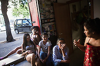 "ROME, ITALY - 3 JULY 2016: Gipsy Queens members Darmaz Florentina (33, right) and Aninfa Hokic (31, 2nd from left) chat during a break together with Darmaz's daughter Grazia (12, center) and two volunteers Francesca (left) and her mother Maria (2nd from right), before heading to their food stand at the iFest, an alternative music festival, in the Astra 19 social center in Rome, Italy, on July 3rd 2016.<br /> <br /> The Gipsy Queens are a travelling catering business founded by Roma women in Rome.<br /> <br /> In 2015 Arci Solidarietà, an independent association for the promotion of social development, launched the ""Tavolo delle donne rom"" (Round table of Roma women) to both incentivise the process of integration of Roma in the city of Rome and to strengthen the Roma women's self-esteem in the context of a culture tied to patriarchal models. The ""Gipsy Queens"" project was founded by ten Roma women in July 2015 after an event organised together with Arci Solidarietà in the Candoni Roma camp in the Magliana, a neighbourhood in the South-West periphery of Rome, during which people were invited to dance and eat Roma cuisine. The goal of the Gipsy Queen travelling catering business is to support equal opportunities and female entrepreneurship among Roma women, who are often relegated to the roles of wives and mothers."