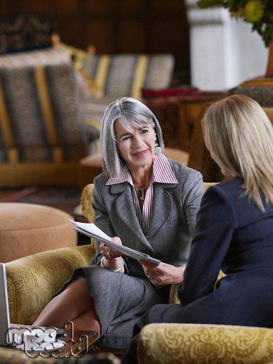 Two business women sitting in lobby looking at documents