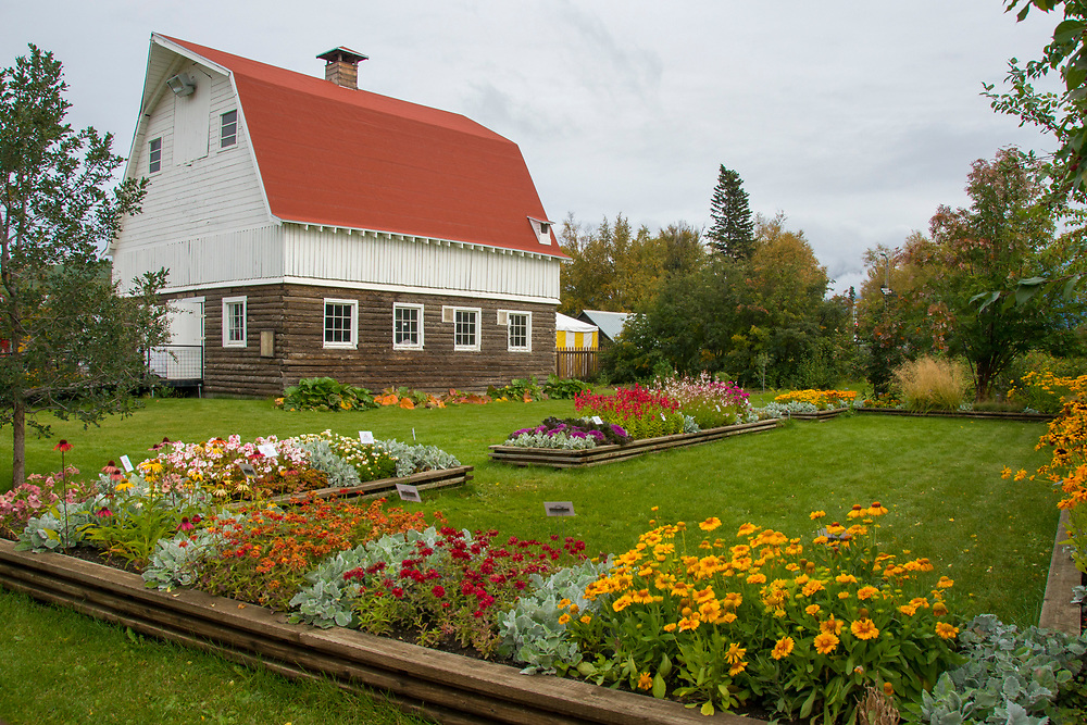 A tranquil garden filled with various blooming flowers alongside a modernized barn.
