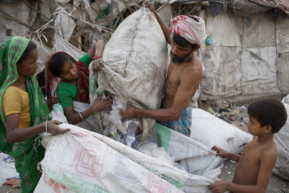 A child helps his family sort out rubbish outside their home.<br />