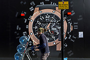 A passing water delivery man wheels bottles past the construction hoarding of a watch outside the new Richard Mille shop in Bond Street, on 19th February 2019, in London, England.
