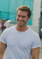 Handsome man smiling  with facial stubble and a white tee shirt