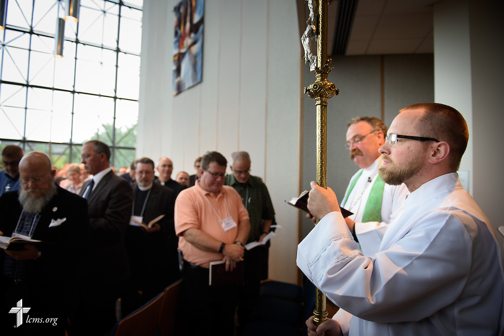 Jon Kohlmeier, communications and technology coordinator at LCMS Iowa District-East, carries the processional cross as crucifer at worship during floor-committee weekend at the International Center of The Lutheran Church–Missouri Synod on Saturday, May 28, 2016, in Kirkwood, Mo. Next to him is the Rev. Dr. Matthew C. Harrison, president of the LCMS. LCMS Communications/Erik M. Lunsford