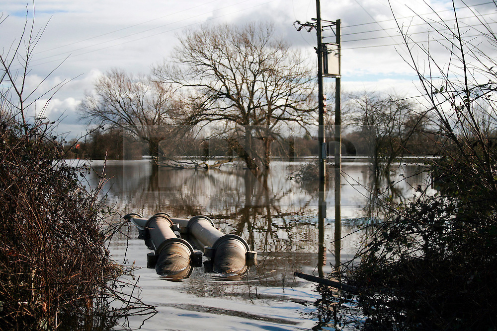 © London News Pictures. 24/02/2014. Moorland, UK. Flood water being pumped from land in Moorland on the Somerset Levels, which continues to suffer from sever flooding. Photo credit: Jason Bryant/LNP