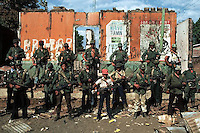 --- Guerrillas pose in front of destroyed police station after taking San Augustin, El Salvador. --- Image by © Owen Franken