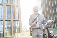 Thoughtful businessman standing with bicycle outside building