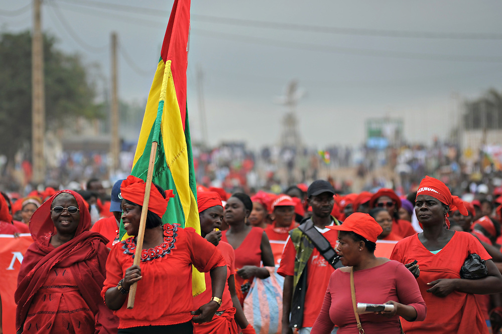 LOME, TOGO - 12-09-20   - Eliane Amegah hoists the Togolese flag. Approximately 300 women dressed in red marched through the Togolese capital city of Lomé on Thursday, September 20 as part of a protest organized by the opposition coalitions Lets Save Togo (Collectif Sauvons le Togo, CST) and Coalition ARC-EN-CIEL.  Several thousand men and youths joined the women in the peaceful march, which ended at an opposition rally point.  Photo by Daniel Hayduk/ AFP