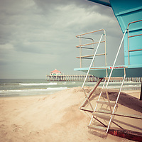 Photo of Huntington Beach Pier and lifeguard stand with storm clouds.