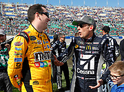 Kyle Busch, left, and Jamie McMurray, right, visit before the start of a NASCAR Cup Series auto race at Kansas Speedway in Kansas City, Kan., Sunday, Oct. 22, 2017. (AP Photo/Colin E. Braley)