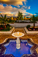 A moorish fountain with the Alhambra palace in background,  Granada, Granada Province, Spain.