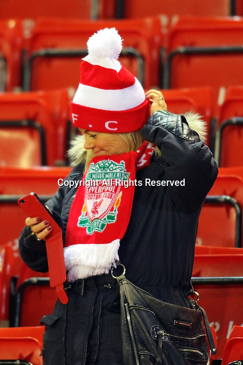 20.01.2015.  Anfield, Liverpool, England. Capital One Cup Semi Final. Liverpool versus Chelsea. A Liverpool supporter looks at her mobile phone pre-game