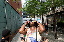 August 21, 2017 - An African American woman peers  through her solar filtered glasses to look at the sun during a solar eclipse in New York city.