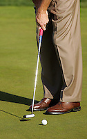 December 2005: Golf ball being putted into the hole with feet and proper golf form in play. Art, graphic, detail,sport, stock, green, shoes, fashion, club.