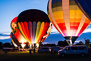 As dusk falls to night, burner flames illuminate several hot air balloons during a balloon glow event, part of the Monroe Balloons and Blues Festival at the Green County fairgrounds in Monroe, Wis., during summer on June 18, 2016. (Photo by Jeff Miller, www.jeffmillerphotography.com)