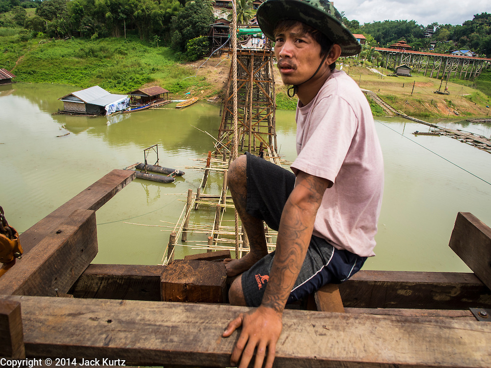 16 SEPTEMBER 2014 - SANGKHLA BURI, KANCHANABURI, THAILAND: A member of the Mon community works on the repair of the Mon Bridge. The 2800 foot long (850 meters) Saphan Mon (Mon Bridge) spans the Song Kalia River. It is reportedly second longest wooden bridge in the world. The bridge was severely damaged during heavy rainfall in July 2013 when its 230 foot middle section  (70 meters) collapsed during flooding. Officially known as Uttamanusorn Bridge, the bridge has been used by people in Sangkhla Buri (also known as Sangkhlaburi) for 20 years. The bridge was was conceived by Luang Pho Uttama, the late abbot of of Wat Wang Wiwekaram, and was built by hand by Mon refugees from Myanmar (then Burma). The wooden bridge is one of the leading tourist attractions in Kanchanaburi province. The loss of the bridge has hurt the economy of the Mon community opposite Sangkhla Buri. The repair has taken far longer than expected. Thai Prime Minister General Prayuth Chan-ocha ordered an engineer unit of the Royal Thai Army to help the local Mon population repair the bridge. Local people said they hope the bridge is repaired by the end November, which is when the tourist season starts.    PHOTO BY JACK KURTZ