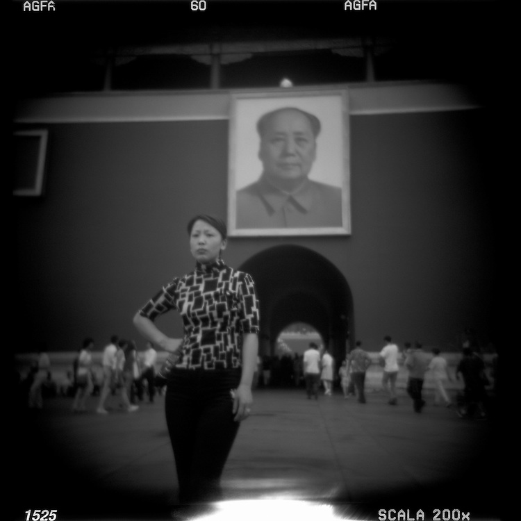 Asia, China, Beijing, Blurred black and white Holga  image of young woman posing for snapshots at the Gate of Heavenly Peace in the Forbidden City on summer afternoon