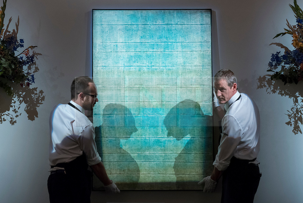 """© Licensed to London News Pictures. 13/10/2016. London, UK. Sotheby's technicians show """"Untitled, 1973"""" by Vasudeo S. Gaitonde (est. GBP 0.9-1.4m) at the preview of Sotheby's Art of the Middle East and India exhibition, which presents artworks to be sold in New Bond Street in four sales in October. Photo credit : Stephen Chung/LNP"""
