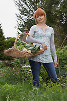 Woman holding vegetable basket in garden portrait