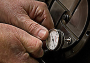 Detail of a machinist or technician taking a measurement with a specialized tool for editorial and advertising photography in an industrial environment.