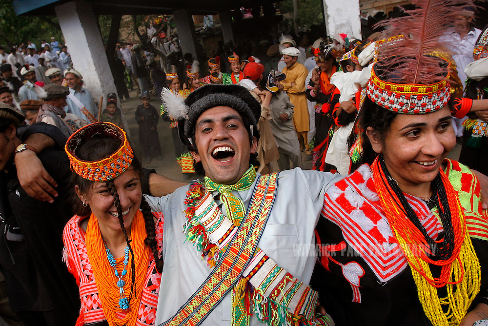 """KALASHA VALLEYS, PAKISTAN - MAY 16: A Kalash man laughs while dancing with women during the """"Joshi"""" (spring) festival in the village of Batrik May 16, 2008 in the Kalasha Valleys, northwestern Pakistan. In stark contrast with the rest of Pakistan, physical contact and socializing between the sexes - of all ages - is encouraged in the Kalash community. The Joshi Festival is a celebration of dance, music and prayer to welcome the coming of warmer season and the new life and crops it brings. The shrinking Kalash community of 4000, who claim to be descendants of Alexander the Great and worship several gods, are considered by many Pakistanis to be unclean, lazy and heretics. They often face ridicule and persecution for their polytheistic religion and fear the spread of hard-line Islamism bordering their communities. (Photo by Warrick Page)"""
