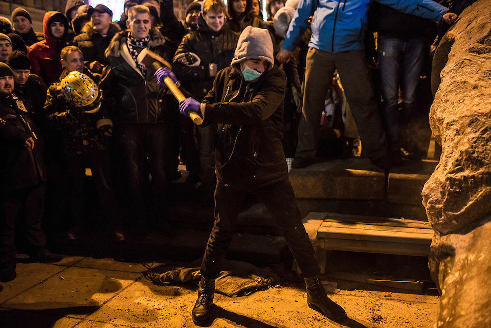 Anti-government protesters used a sledge hammer to destroy a statue of Russian communist revolutionary leader Vladimir Lenin, which they tore down following a massive rally in Independence Square.