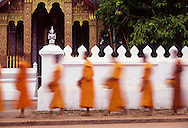 Monks dressed in orange robes recieve alms (collect the day's offerings) from generous locals of Luang Prabang, Loas. Luang Prabang has the highest concentration of monks per population in the country.