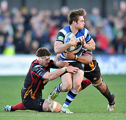 Tom Heathcote (Bath) is double-tackled - Photo mandatory by-line: Patrick Khachfe/JMP - Tel: Mobile: 07966 386802 11/01/2014 - SPORT - RUGBY UNION -  Rodney Parade, Newport - Newport Gwent Dragons v Bath - Amlin Challenge Cup.