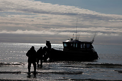 Group of male adults disembark from a boat along a beach, Cook Inlet, Lake Clark National Park, Alaska, United States of America