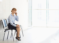 Businesswoman using cell phone while sitting on chair in office