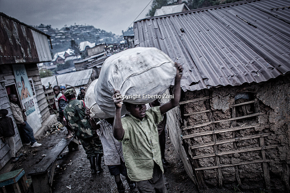 Democratic Republic of Congo, North Kivu. Coltan and manganese are rare metals used to make mobile phones and computers. The market value is so high as to have aroused the interest of criminal organizations, in order to destabilize the political situation and take control of the mining business at a reasonable price, financial backing is given to armed groups waging war on one another. Nyatura soldiers control the territory, exploiting the local population and reselling its natural resources: the proceeds are used to buy other weapons that provide additional power, thus creating a vicious circle it is difficult to break. Nyatura survive by bullying, through abuse of power, abuse of civilians, raiding night and day and demanding tax on all forms of activity in the city of Rubaya. Soldiers patrol the territory around the Mudere mine where miners dig 20 meters underground. After workers transporting minerals to a nearby river where they are separated from rocks and sand before being sold to dealers.