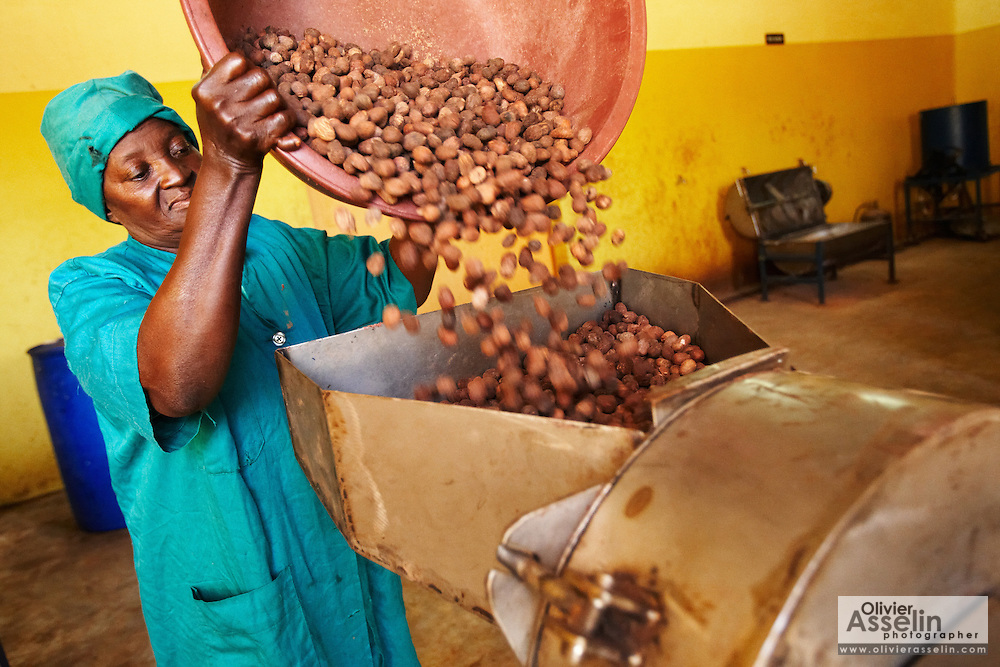 A woman pours shea nuts into a grinder at the Si Yiriwa shea processing center in the town of Diolila, Mali on Friday January 15, 2010.