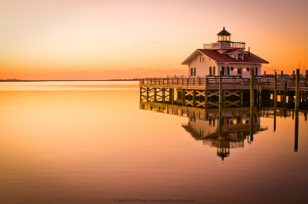 roanoke marshes light stands in perfect reflection as the sun begins to rise
